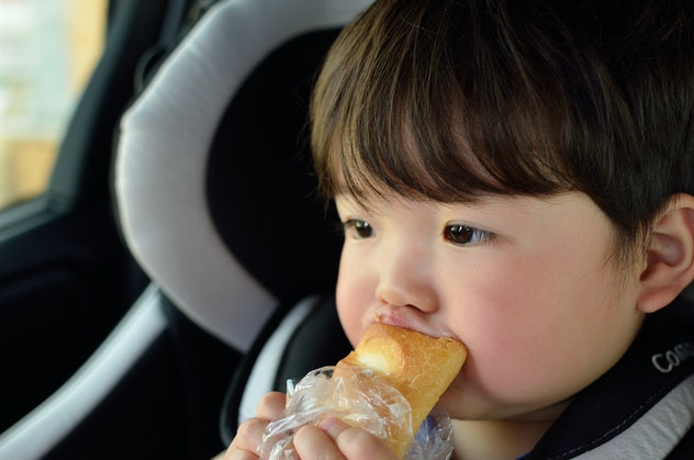 Child rides on a child seat and eats bread