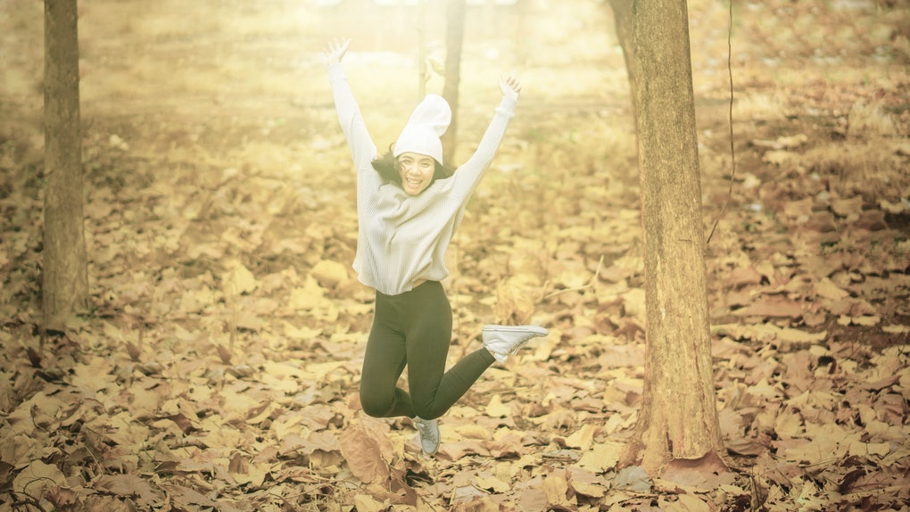 Picture of young man looks happy while jumping in the autumn park with dried autumn foliage