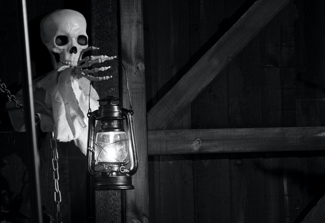 Droitwich Spa, Worcester, England, United Kingdom, 02/10/2019, Ghost Tours, Skeleton holding a lit oil lamp against a wooden structure at night. Halloween, Ghost stories and Ghost tours.