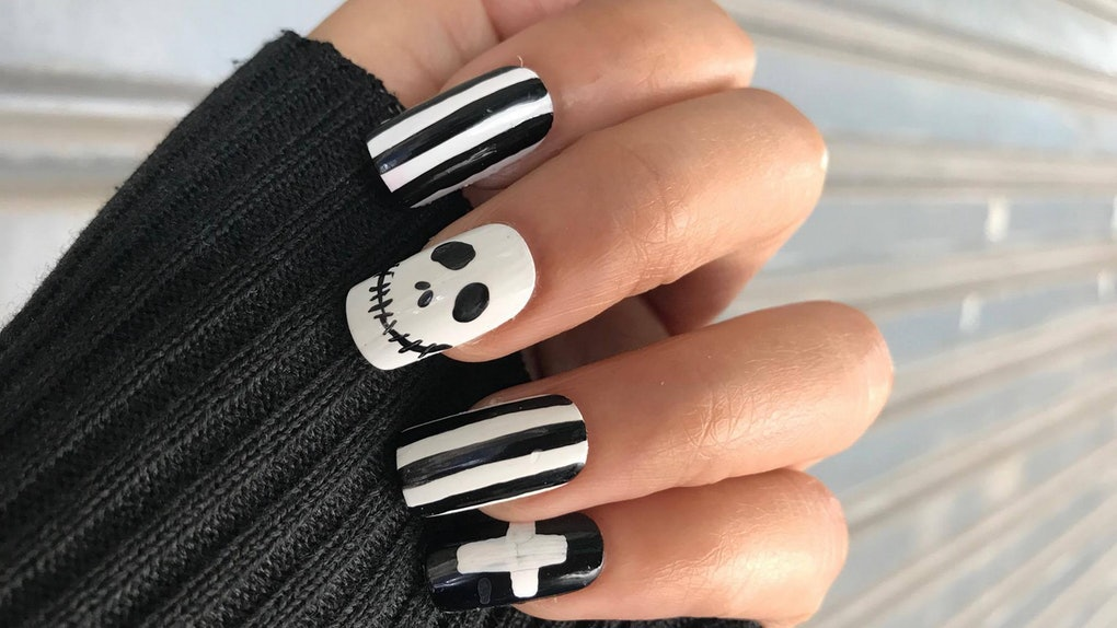 A woman's hand has black and white square-shaped nails decorated with inspirations from 'The Nightmare Before Christmas' for a spooky Halloween nail art pic.