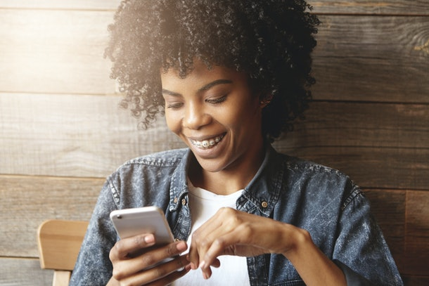 Indoor shot of dark-skinned girl with cute smile and braces enjoying free wi-fi at coffee shop, surfing internet on mobile phone, messaging friends online, inviting them to party at her place tonight