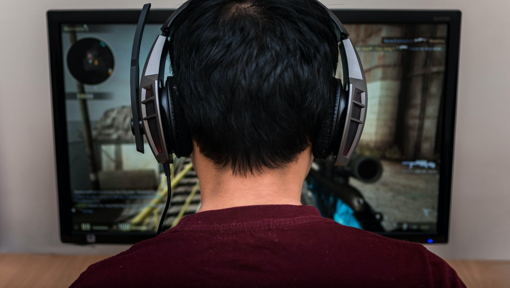 Gamer in headphone playing video game at home.