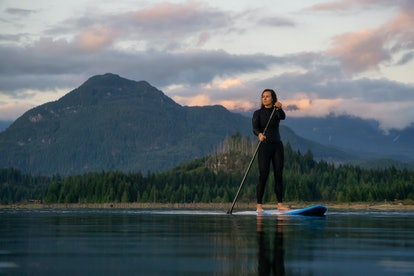 Adventurous Girl on a Paddle Board is paddling in a calm lake with mountains in the background durin...
