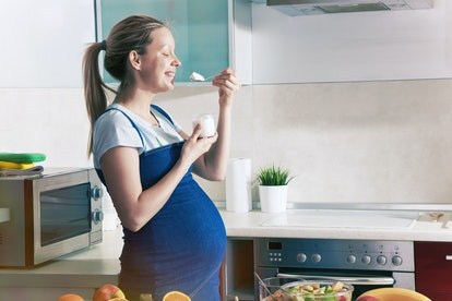 pregnant woman eating milky yogurt in morning healthy breakfast