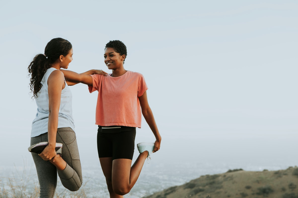 Two friends smile and stretch together in workout clothes outside.