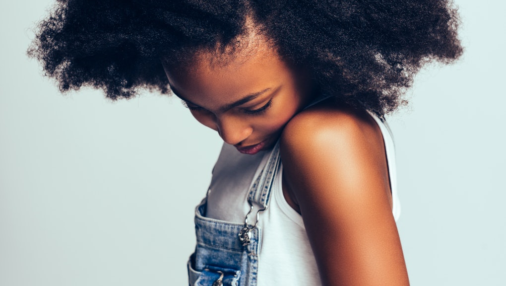 Shy little African girl with long curly hair wearing dungarees standing sideways alone against a gray background