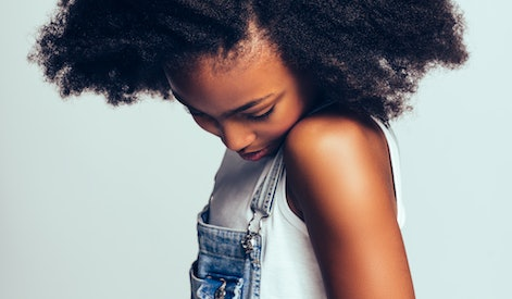 Shy little African girl with long curly hair wearing dungarees standing sideways alone against a gra...