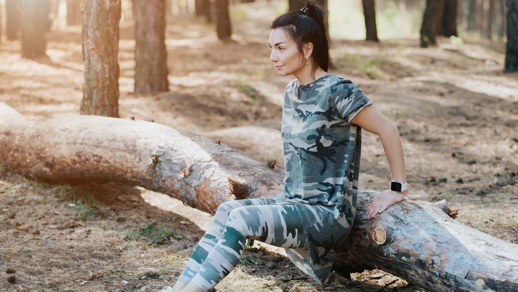 A brunette woman wearing camo shirt and leggings works out in the woods.