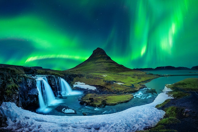 Iceland is perfect for a winter getaway, and you may see the Northern Lights in the process, like here at Kirkjufell Mountain.