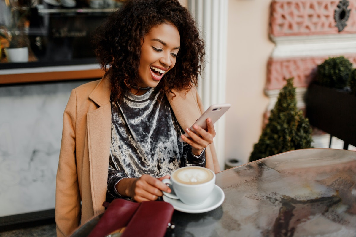 A stylish girl laughs while looking at her phone in a cute café with a pumpkin coffee on the table.