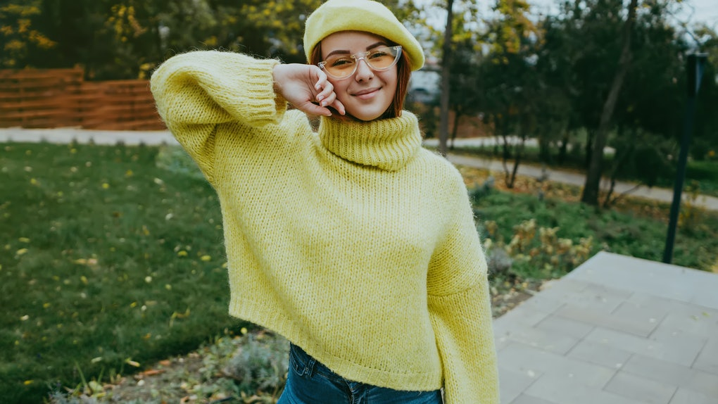 Autumn woman in autumn park. Warm sunny weather. Fall concept.Close up image of happy red hair woman in sunglasses and autumn clothes posing sideways outdoors