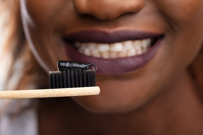 Close-up Of Young Woman Holding Tooth Brush With Black Active Charcoal Toothpaste