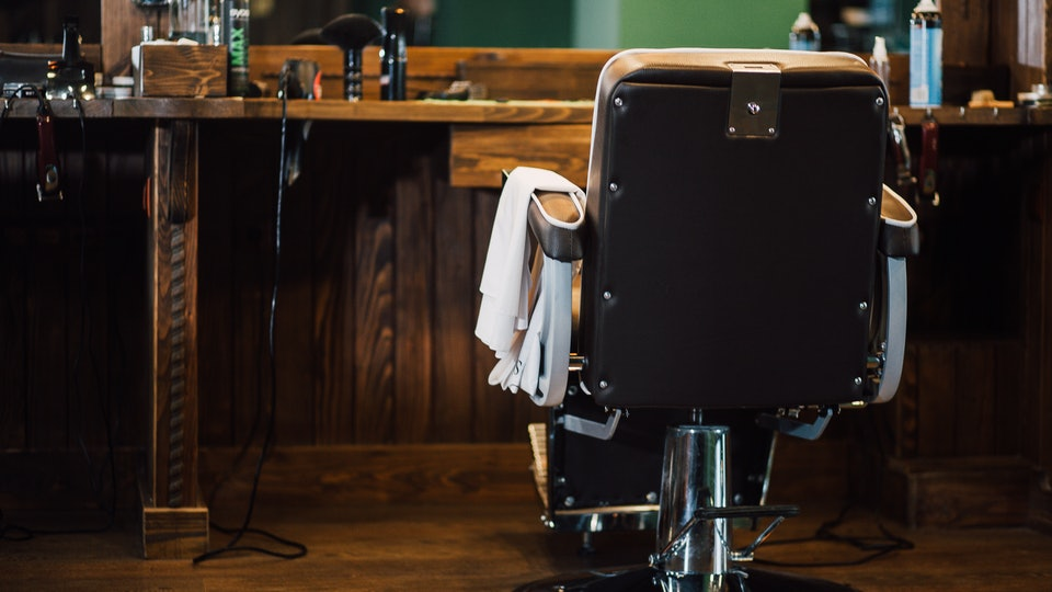 A barber chair sits in an empty barbershop.