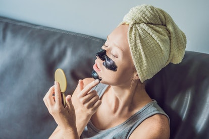 Beautiful young woman relaxing with face mask at home. Happy joyful woman applying black mask on face