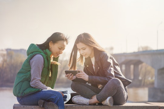 Two teenagers look at a phone together.