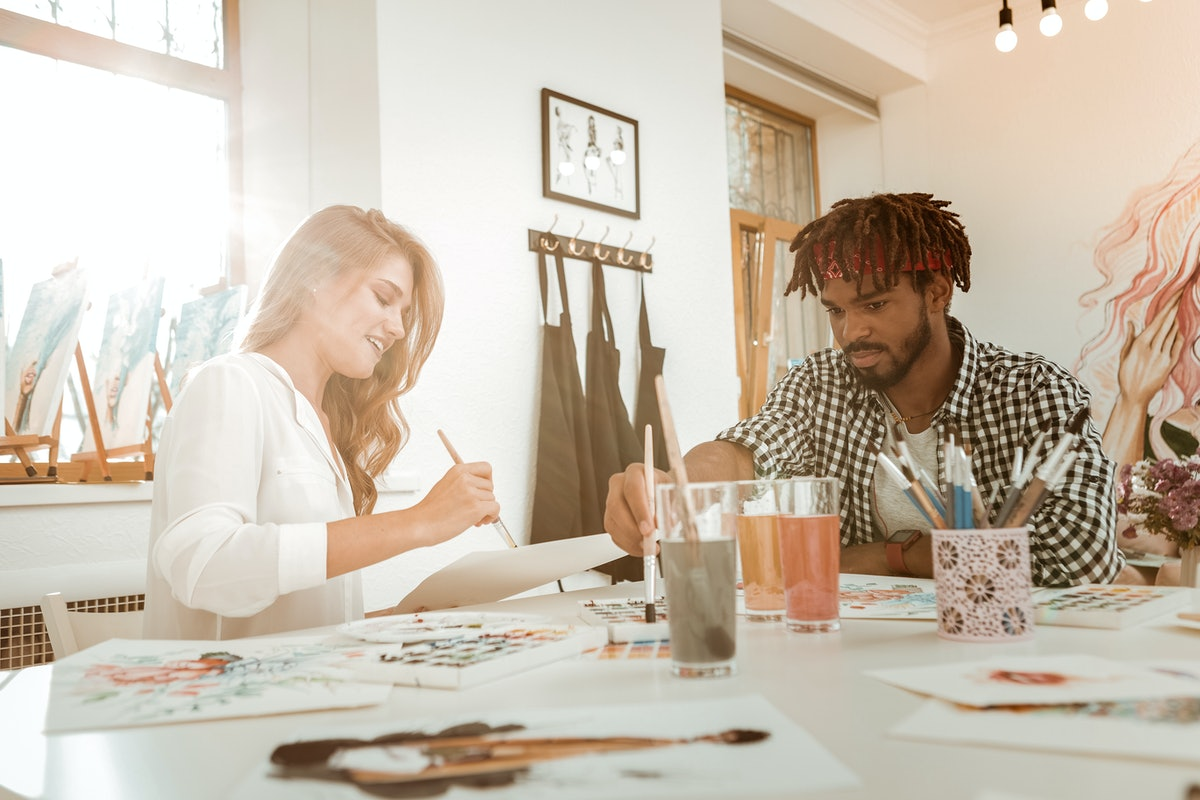Drawing together. Couple of talented young artists using watercolors while drawing together