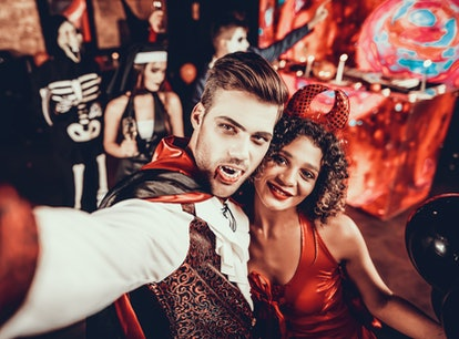 Young couple in Halloween costumes taking a selfie.