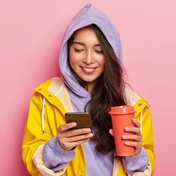 Indoor shot of happy dark haired girl wears hoody and raincoat, holds mobile phone, scrolls feed in socian networks, drinks coffee or tea isolated on pink background. Using technology during rainy day