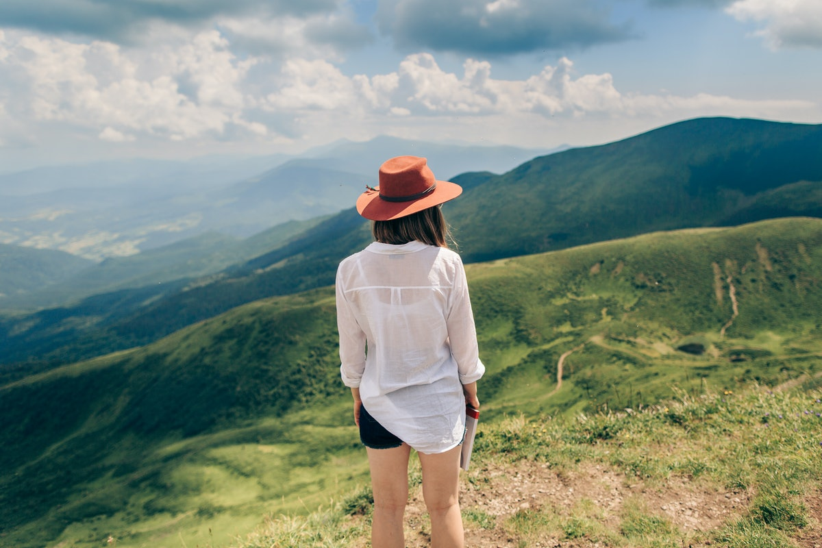 Woman in hat standing back. Mountains background