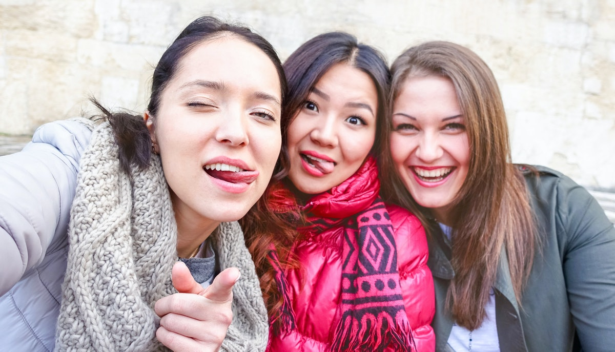 Young women taking selfie warning you - Teenage girls fun moments doing funny faces tongue out - Be...