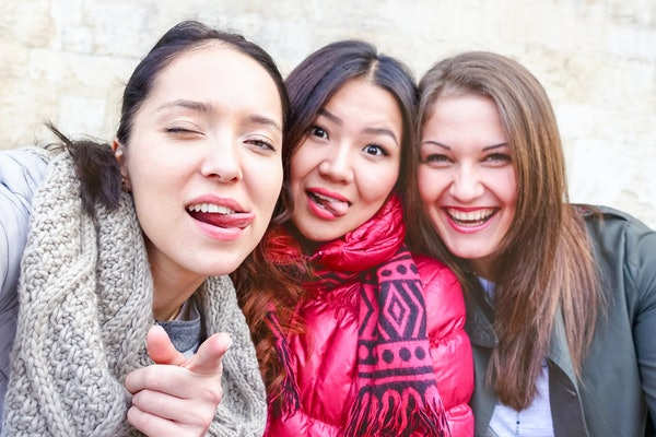 Young women taking selfie warning you - Teenage girls fun moments doing funny faces tongue out - Best female friends outdoors on cold winter day - Friendship concept - Focus on left subject