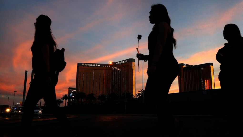 People carry flowers as they walk near the Mandalay Bay hotel and casino during a vigil for victims and survivors of a mass shooting in Las Vegas, in Las Vegas. Sunday marked six months since the shooting along the Las Vegas Strip, when a gunman shot from the hotel and killed over 50 people and injured hundreds of others