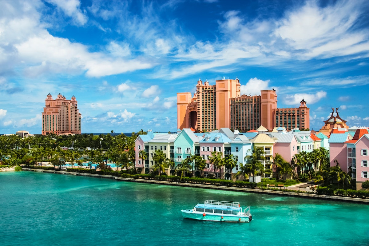 Beautiful scene of a boat, ocean, colorful houses and a hotel in Nassau, Bahamas on a summer sunny d...