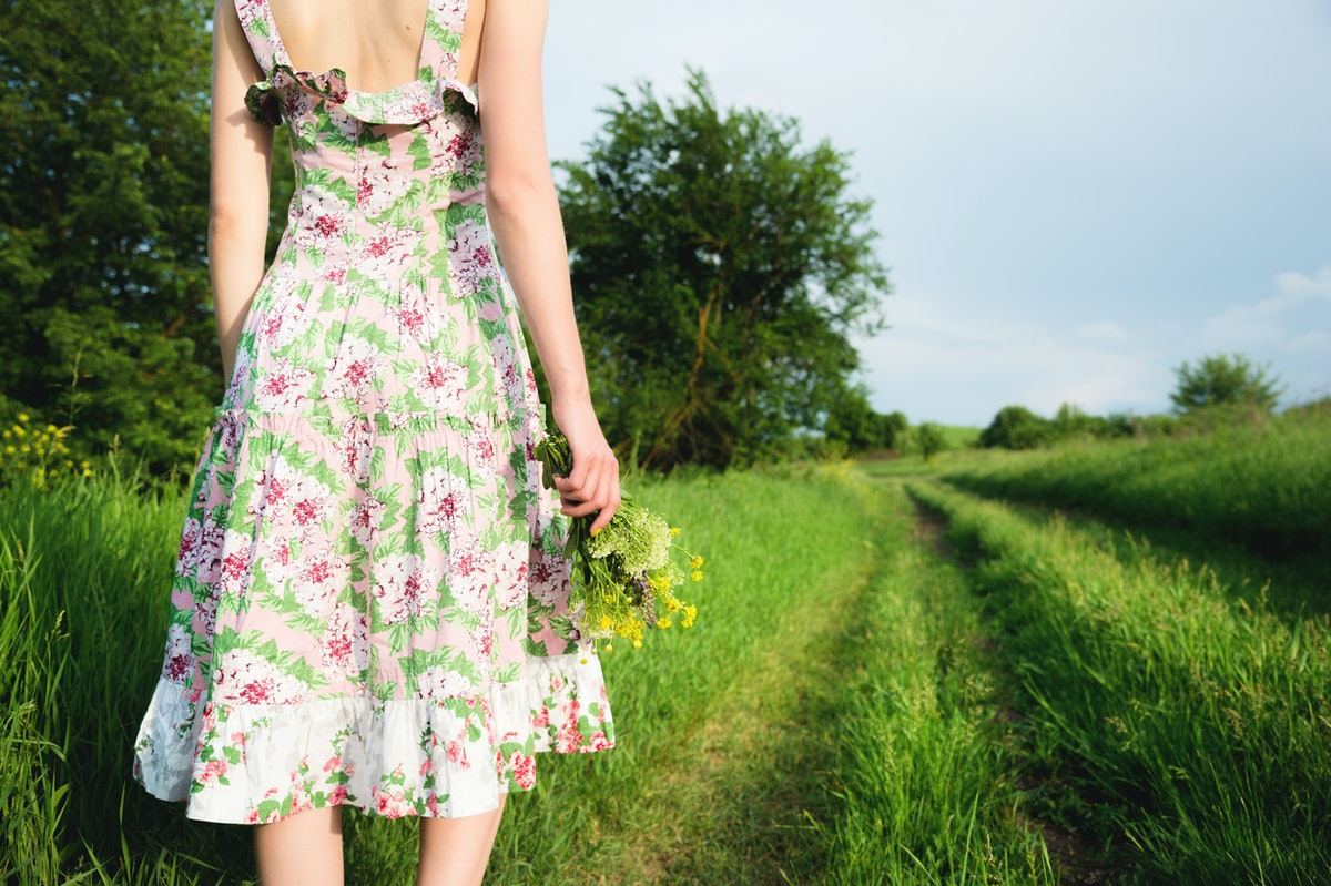 A view from the back of a girl in a light summer dress with a bouquet of wildflowers is standing in ...