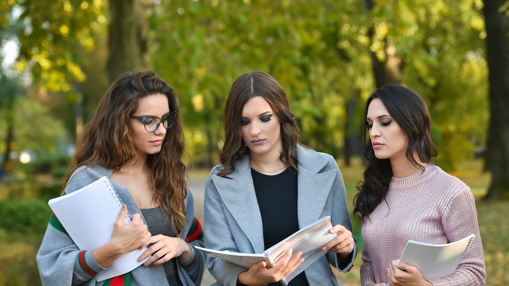 three student woman with textbook in a park in autumn