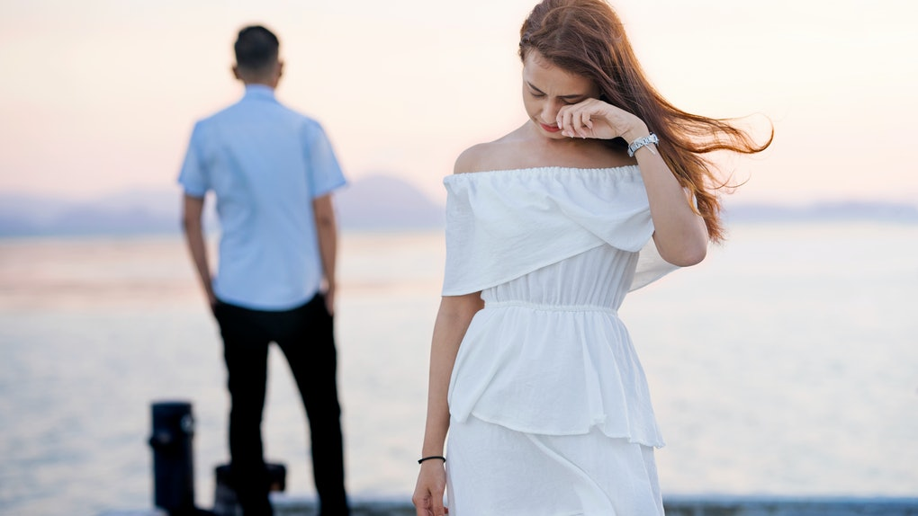 Young couple break up at the sea deck. Girl crying and walk away from man in concept love hurts,hard relationship,sad love story,when love is ended. Broken heart syndrome. How to fix a broken heart.