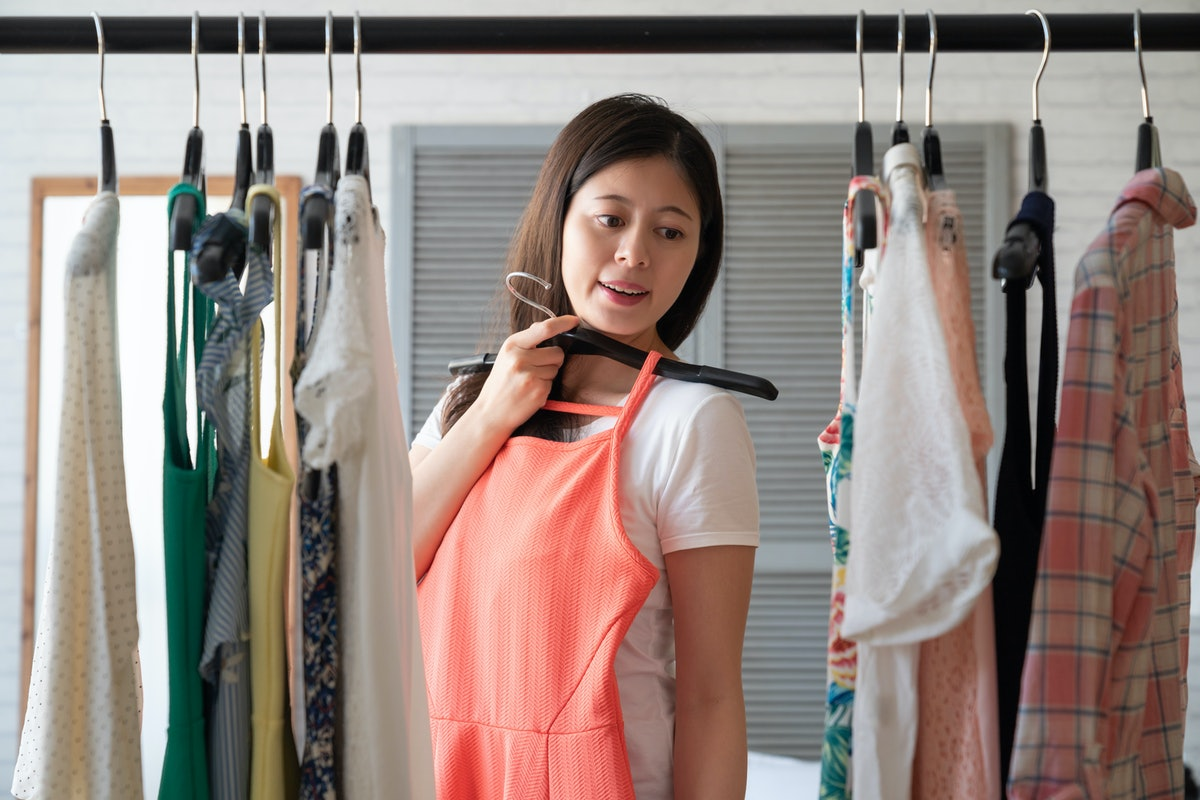 clothing wardrobe fashion, style and people concept. happy asian woman with dress on hanger looking ...
