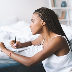 concentrated african american woman with laptop in bed writing in notepad