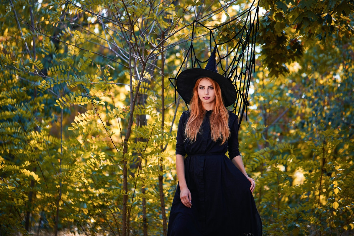 Young woman in Halloween witch costume for your Scorpio season 2019 horoscope.