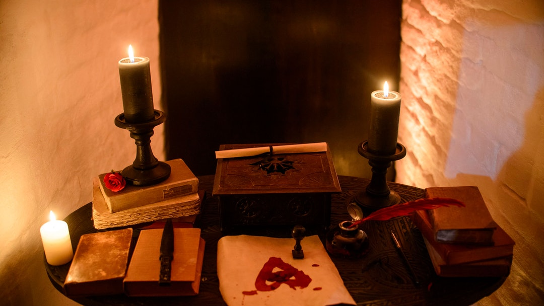 In this picture taken, candles and books are arranged on a table before a photo shoot of a room in Bran Castle, in Bran, Romania. Airbnb has launched a contest to find two people to stay overnight in the castle on Halloween, popularly known as Dracula's castle because of its connection to the cruel real-life prince Vlad the Impaler, who inspired the legend of Dracula