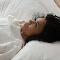 Thoughtful african American millennial girl lying in white comfortable bed lost in thoughts think of...