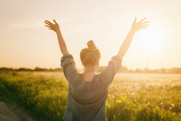 female teen girl stand feel freedom with arms stretched to the sky