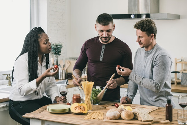African American woman with two Caucasian men cooking salad together in kitchen at home on weekend
