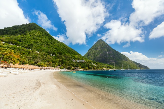 Idyllic white sand tropical beach with view to Piton mountains in Saint Lucia Caribbean