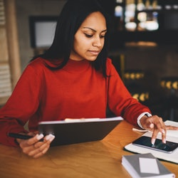 Afro american hipster girl dressed in red sweatshirt checking email on modern telephone device working on new creative project sitting in coffee shop interior.Student making training schedule