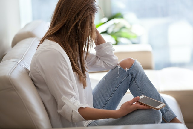 Jealous woman sitting on sofa holding phone feeling sad waiting for call, frustrated millennial girl upset or worried receiving bad news in mobile message on smartphone at home, cyberbullying concept