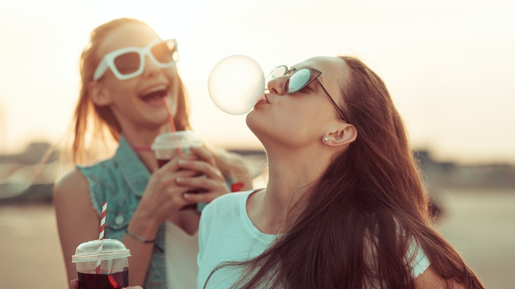 Two girls wearing sunglasses hold their iced coffee while one blows a bubblegum bubble at sunset.