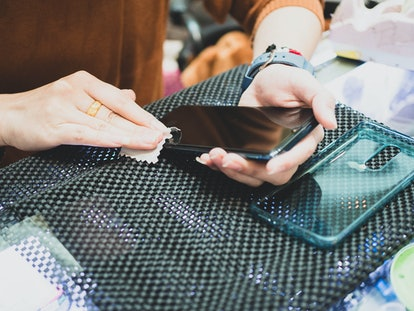 Women cleaning phone,female holding phone and  cleaning on screen phone,selective focus.