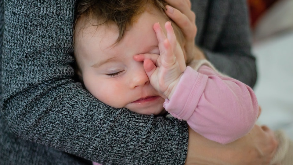 tired baby rubbing her eyes