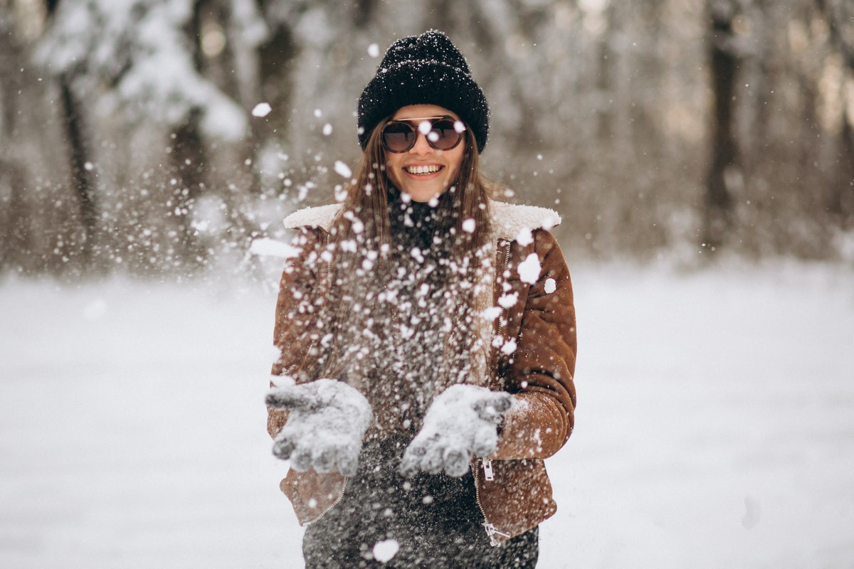 A woman in sunglasses, beanie cap, and jacket smiles and plays outside on a snow day.