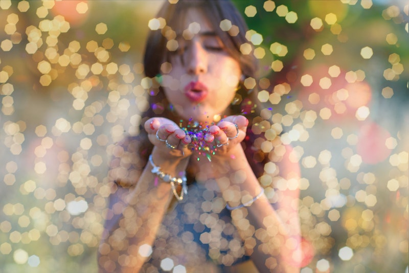 Young beautiful women blowing colorful confetti stars from hands. Celebration and event concept. Moment of Really true joy of being alive.