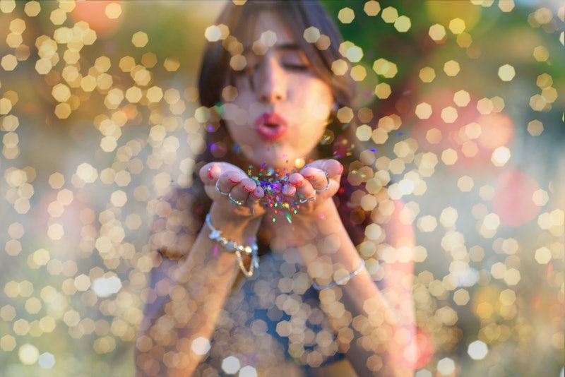 Young beautiful women blowing colorful confetti stars from hands. Celebration and event concept. Mom...