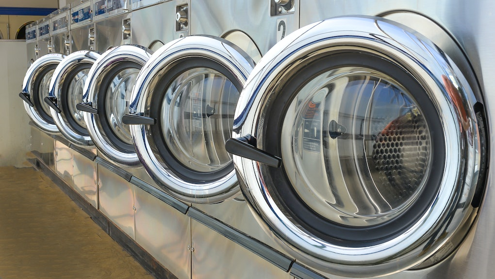 Row of industrial laundry machines in laundromat.