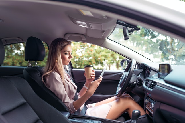 woman driving car summer city, parking lot traffic jam while waiting, looks phone, reads and writes message her smartphone. Long hair formal suit business lady. Cup coffee, tea, drink, snack lunch
