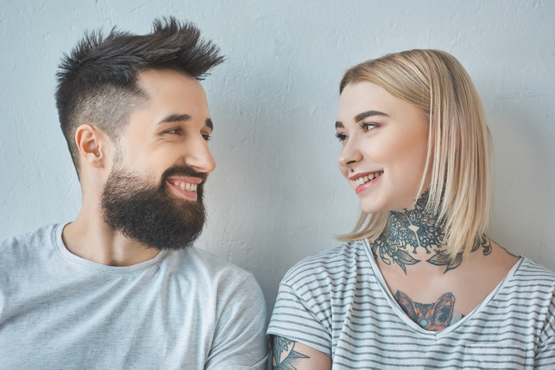 portrait of smiling couple with tattoos looking at each other