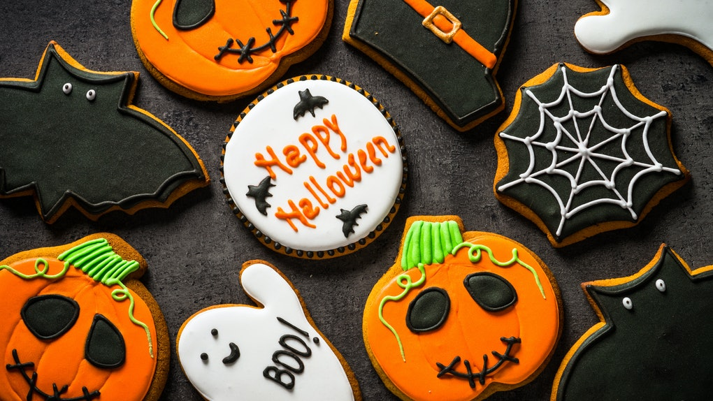 A spread of Halloween cookies, including ones decorated like ghosts, bats, witch hats, and pumpkins, against a black background.